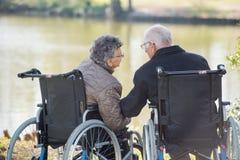Oude paarzitting op hun rolstoelen stock afbeelding