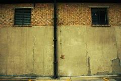 Oude pakhuisbakstenen muur met twee vensters Stock Afbeelding