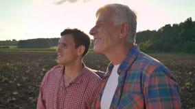 Oude papa die zijn zoon omhelzen en gecultiveerd gebied, mooie mening op achtergrond tijdens zonsondergang bekijken, lensgloed stock footage