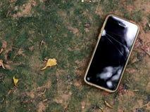 Oude plattelander gebroken slimme telefoon in vuil siliconegeval die op de vloer leggen Stock Foto's