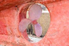 Oude propeller van een rode vissersboot stock afbeelding