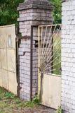 Oude rachitische roestige poort en metaal gele wicket met een slot tussen de twee baksteenpijlers royalty-vrije stock afbeeldingen