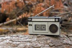 Oude radio en cassetterecorder op een tak in het hout Stock Afbeelding