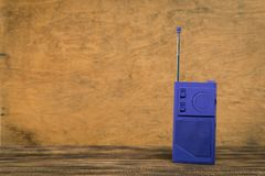 Oude radio op houten lijst met de achtergrond van de kleurenmuur stock foto