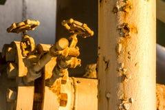 Oude raffinaderij met roestige pijpenzonsondergang Royalty-vrije Stock Afbeeldingen