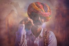 Oude Rajasthani-mens tegen de achtergrond van zijn kamelen Royalty-vrije Stock Foto
