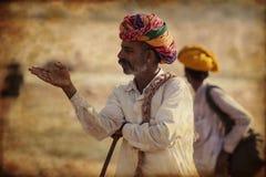 Oude Rajasthani-mens tegen de achtergrond van zijn kamelen Stock Afbeelding