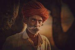 Oude Rajasthani-mens tegen de achtergrond van zijn kamelen Royalty-vrije Stock Afbeelding