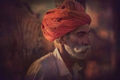 Oude Rajasthani-mens tegen de achtergrond van zijn kamelen Royalty-vrije Stock Foto's