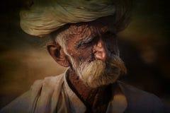 Oude Rajasthani-mens tegen de achtergrond van zijn kamelen Stock Fotografie