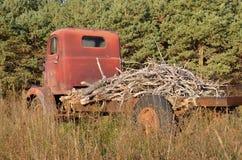 Oude rammelkastvrachtwagen achter elkaar die met takken wordt geladen Royalty-vrije Stock Foto's
