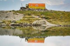 Oude reddingsschuilplaats op de kust van een ijzig bergmeer stock foto's