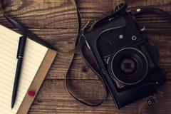 Oude retro camera met gevoerd notitieboekje en pen op uitstekende houten B Royalty-vrije Stock Fotografie