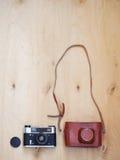 Oude retro camera met leergeval op houten achtergrond Stock Afbeeldingen