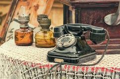 Oude retro objecten antieke telefoon en gaslampen op de lijst stock foto