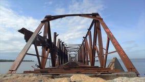 Oude reusachtige verlaten spoorweg roestige brug hierboven - water De kustzomer Gezoem binnen stock videobeelden