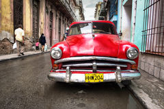 Oude rode auto in een sjofele straat in Havana Stock Afbeeldingen