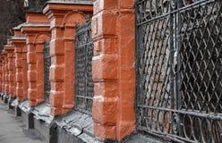 Oude rode baksteen en zwarte roosteromheining stock afbeeldingen