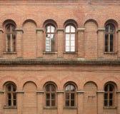 Oude rode bakstenen muur met vensters Royalty-vrije Stock Foto's