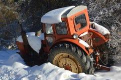 Oude rode die tractor met sneeuw wordt behandeld royalty-vrije stock foto