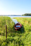 Oude rode houten vissersboot met water bij het meer Stock Afbeelding