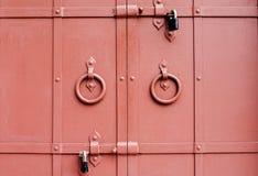 Oude rode poortdeuren met sloten royalty-vrije stock afbeelding