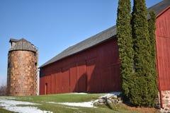Oude rode schuur in de vroege winter met enkel een aanraking van sneeuw op een zonnige dag op een landbouwbedrijf royalty-vrije stock foto