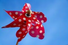 Oude rode stuk speelgoed windmolen met witte punten op blauwe hemel Stock Afbeeldingen