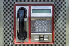 Oude rode telefooncel in doos openlucht in stadsstraat stock afbeeldingen