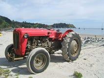 Oude rode tractor op een strand Stock Foto's