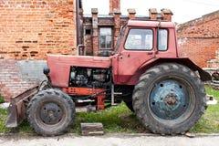 Oude rode tractor op het landbouwbedrijf stock foto's