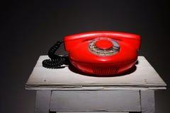 Oude rode uitstekende telefoon op een witte stoelkruk Royalty-vrije Stock Afbeelding