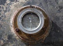 Oude roestige cirkeltemperatuurmaat opgezet op industriële machines stock afbeeldingen