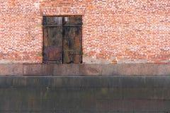 Oude roestige deur op oude bakstenen muurachtergrond stock foto's