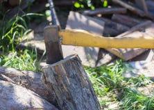 Oude roestige die bijl in een oud logboek, hakkend hout wordt geplakt royalty-vrije stock foto