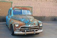 Oude roestige die retro auto dichtbij een bakstenen muur wordt geparkeerd stock fotografie