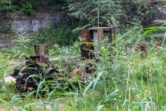 Oude roestige die tractor in de carrière van een oude lens in het gebied van Sverdlovsk wordt verlaten stock foto's