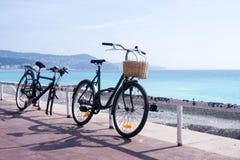 Oude roestige fiets met een rieten mand op de achtergrond van het turkooise overzees Dichtbij een gebroken fiets, zonder wielen stock afbeeldingen