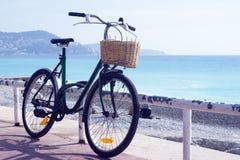 Oude roestige fiets met een rieten mand op de achtergrond van het turkooise overzees stock foto