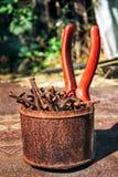 Oude roestige gebroken hulpmiddelen, spijkers en buigtang op een achtergrond van roest Stock Afbeeldingen