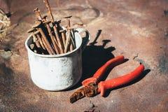 Oude roestige gebroken hulpmiddelen, spijkers en buigtang op een achtergrond van roest Royalty-vrije Stock Foto's