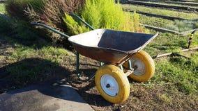 Oude roestige het tuinieren kruiwagen met gele wielen stock foto