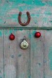 Oude roestige hoef, Kerstmisspeelgoed en uitstekende klok op houten deur stock afbeelding