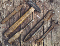 Oude, roestige hulpmiddelen die op een houten lijst liggen Stock Fotografie