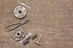 Oude roestige hulpmiddelen en details op de ruwe stof Stock Afbeeldingen