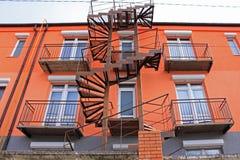 Oude roestige ijzerwenteltrap bij een helder oranje high-rise gebouw royalty-vrije stock afbeeldingen