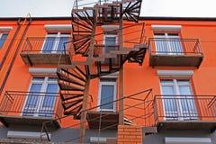 Oude roestige ijzerwenteltrap bij een helder oranje high-rise gebouw stock afbeelding
