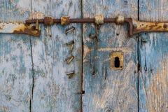 Oude roestige klink op een oude houten deur Stock Afbeelding