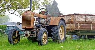 Oude roestige landbouwbedrijftractor met aanhangwagen Royalty-vrije Stock Foto's