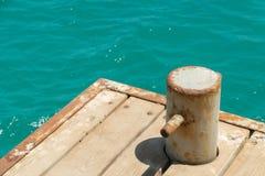 Oude, roestige meerpaal met metaalketting op pijler met water Royalty-vrije Stock Foto's